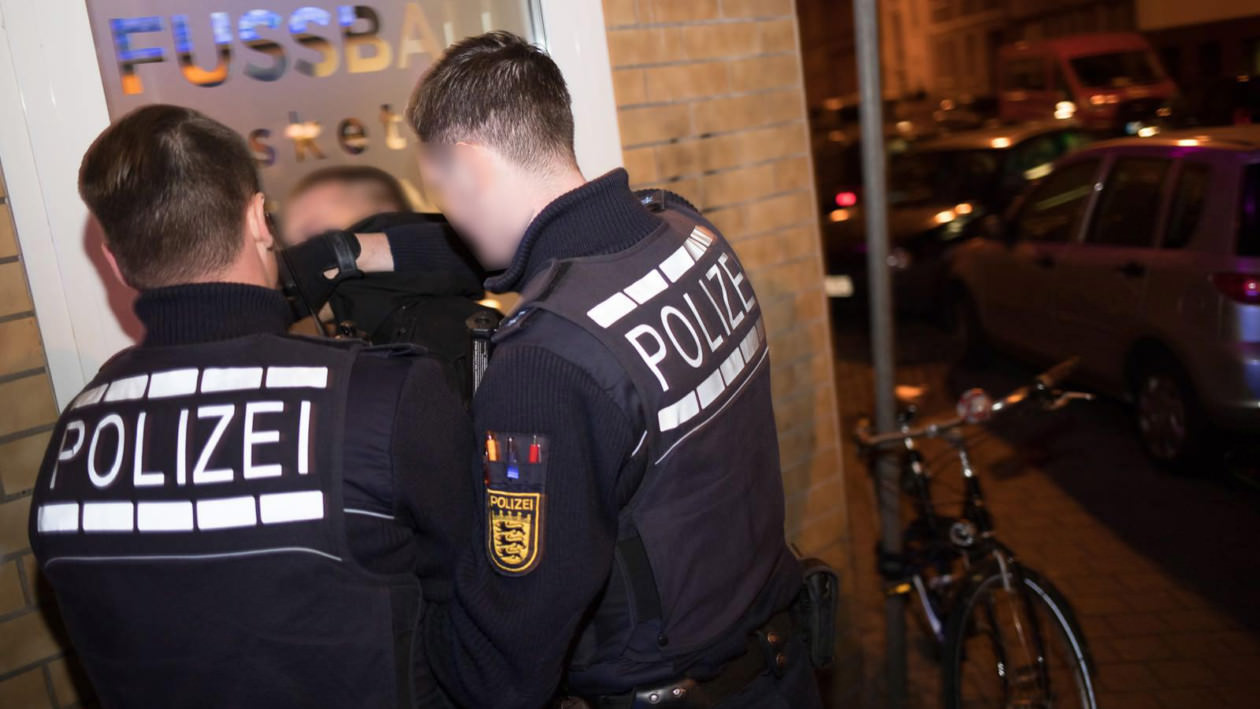 Der Beschuldigte wird an der Ecke Pflügersgrundstraße an der Wand fixiert. Später wird er in das Wettbüro geschleppt   Foto: CKI